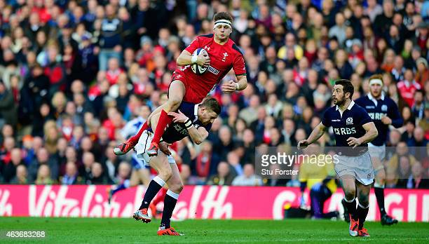 Wales flyhalf Dan Biggar is taken out by Finn Russell of Scotland and subsequently shown a yellow card during the RBS Six Nations match between...