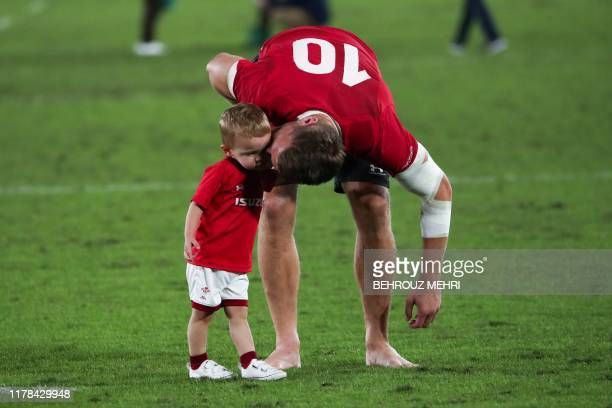 Wales' flyhalf Dan Biggar kisses his son on the pitch after the Japan 2019 Rugby World Cup semifinal match between Wales and South Africa at the...