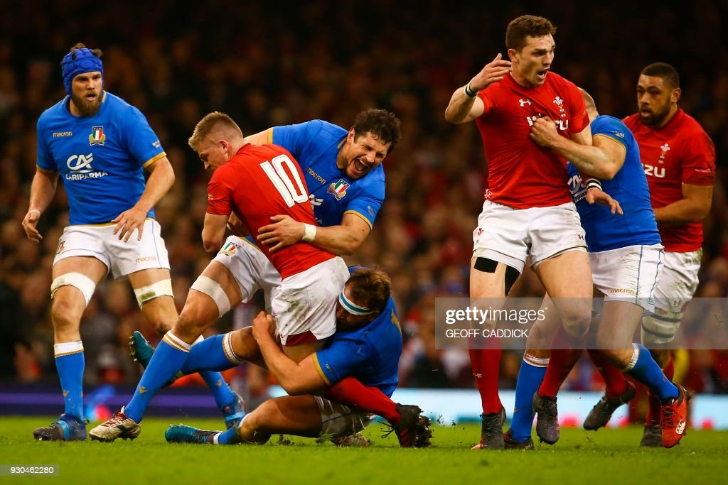 TOPSHOT - Wales' fly-half Gareth Anscombe (2L) is tackled by Italy's lock Alessandro Zanni (3L) during the Six Nations international rugby union match between Wales and Italy at the Principality Stadium in Cardiff, south Wales, on March 11, 2018. / AFP PHOTO / Geoff CADDICK / RESTRICTED TO EDITORIAL USE. Use in books subject to Welsh Rugby Union (WRU) approval.