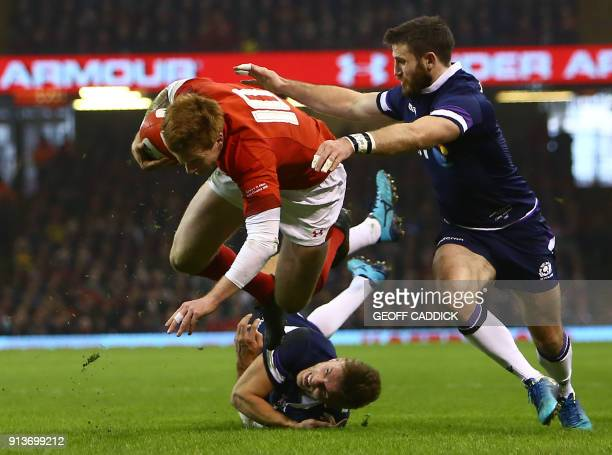 Wales' flyhalf Rhys Patchell is tackled by Scotland's wing Tommy Seymour as Scotland's centre Chris Harris looks on during the Six Nations...