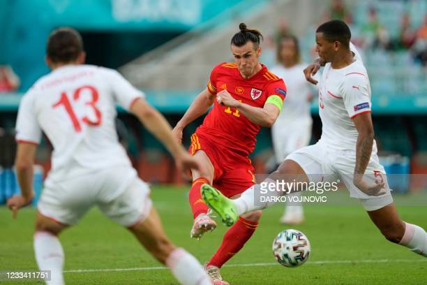 Wales' forward Gareth Bale attempts a shot as he is marked by Switzerland's defender Manuel Akanji during the UEFA EURO 2020 Group A football match...