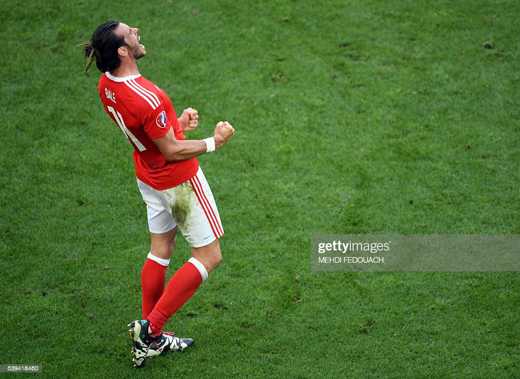 TOPSHOT - Wales' forward Gareth Bale celebrates the team's 2-1 win over Slovakia in the Euro 2016 group B football match between Wales and Slovakia at the Stade de Bordeaux in Bordeaux on June 11, 2016. / AFP / MEHDI