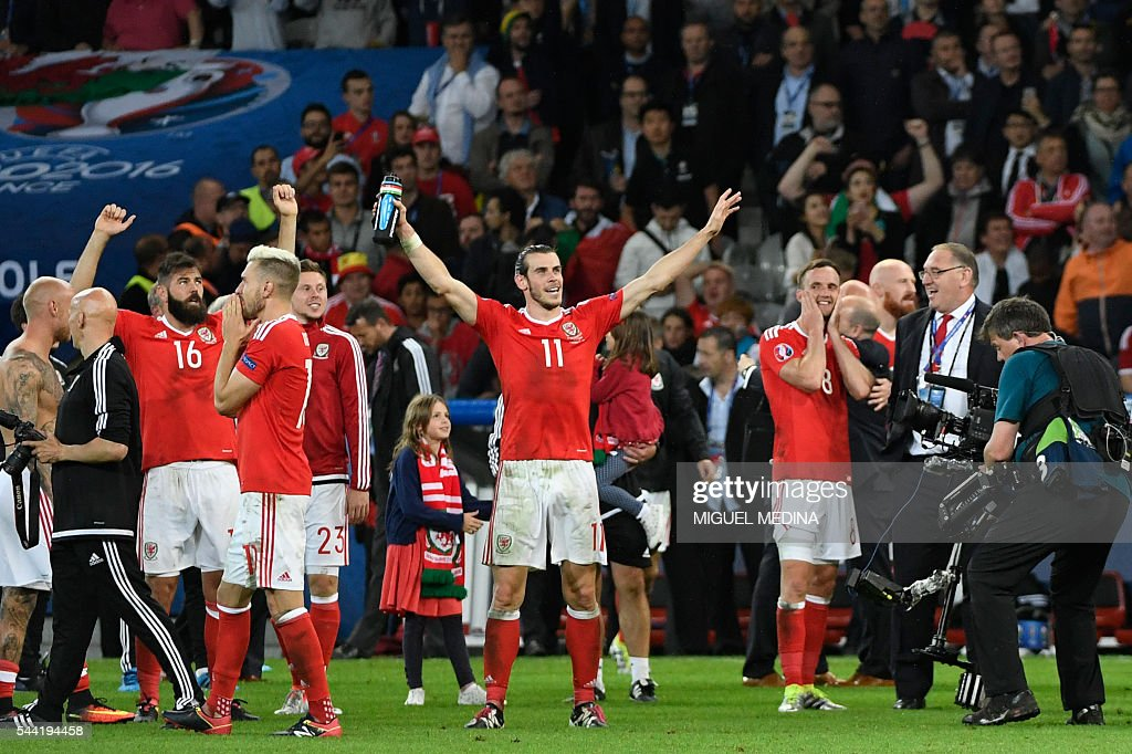 Wales' forward Gareth Bale (C) celebrates with teammates at the end of the Euro 2016 quarter-final football match between Wales and Belgium at the Pierre-Mauroy stadium in Villeneuve-d'Ascq near Lille, on July 1, 2016. / AFP / MIGUEL