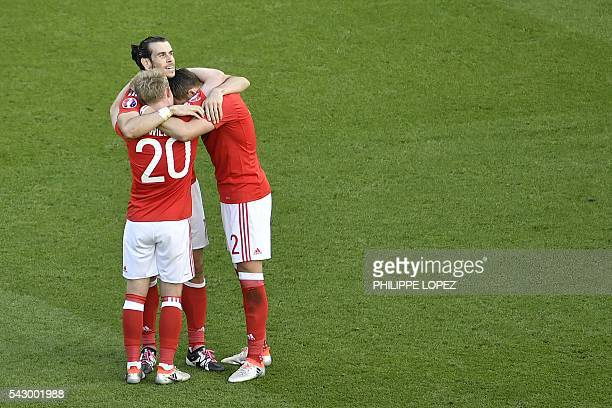 Wales' forward Gareth Bale celebrates with teammates Wales' midfielder Jonathan Williams and Wales' defender Chris Gunter their 10 win in the Euro...