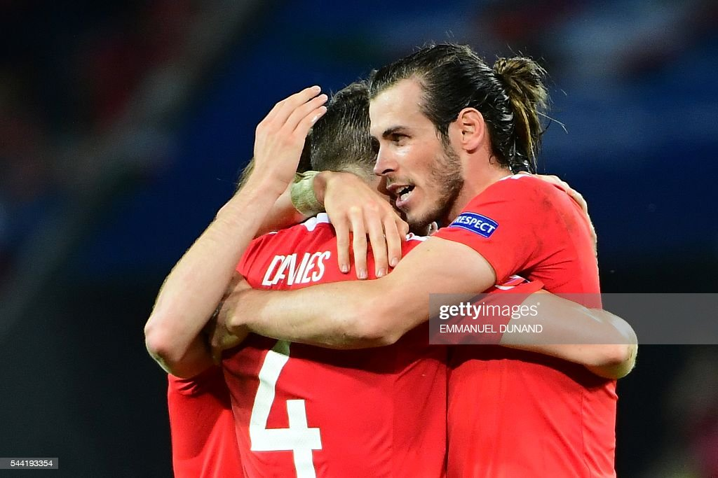 Wales' forward Gareth Bale (R) celebrates with Wales' defender Ben Davies after the Euro 2016 quarter-final football match between Wales and Belgium at the Pierre-Mauroy stadium in Villeneuve-d'Ascq near Lille, on July 1, 2016. Wales won the match 3-1. / AFP / EMMANUEL