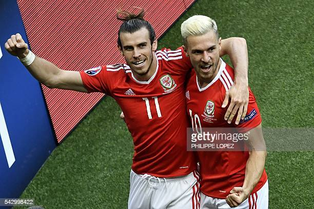 Wales' forward Gareth Bale celebrates with Wales' midfielder Aaron Ramsey following an own goal by Northern Ireland during the Euro 2016 round of...