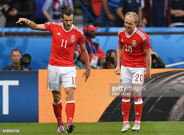 Wales' forward Gareth Bale celebrates with Wales' midfielder Jonathan Williams after Northern Ireland scored an own goal during the Euro 2016 round...