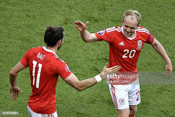 Wales' forward Gareth Bale celebrates with Wales' midfielder Jonathan Williams following an own goal by Northern Ireland during the Euro 2016 round...