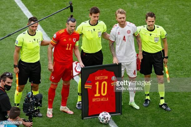 Wales' forward Gareth Bale , Denmark's defender Simon Kjaer and German referee Daniel Siebert pose with a framed Welsh jersey bearing name of...