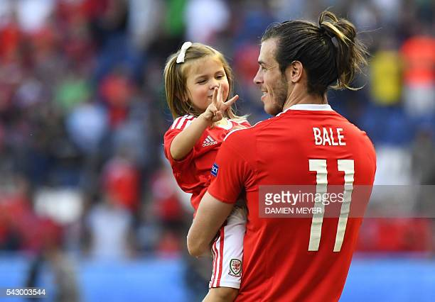 Wales' forward Gareth Bale holds his daughter Alba Viola as he acknowledges the crowds following the team's 10 win in the Euro 2016 round of sixteen...