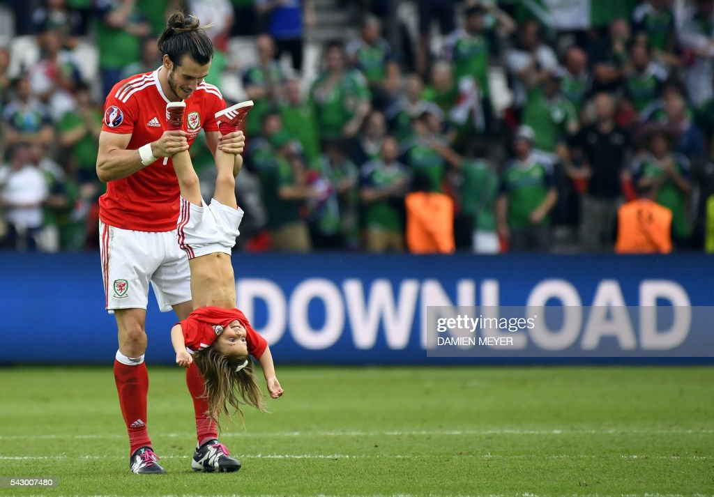 TOPSHOT - Wales' forward Gareth Bale holds his daughter Alba Viola following the Euro 2016 round of sixteen football match Wales vs Northern Ireland, on June 25, 2016 at the Parc des Princes stadium in Paris. /