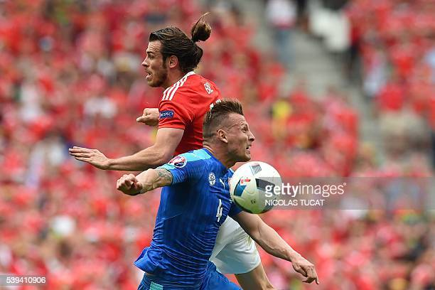 TOPSHOT Wales' forward Gareth Bale jumps for the ball with Slovakia's defender Jan Durica during the Euro 2016 group B football match between Wales...