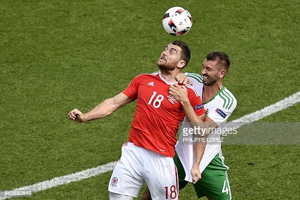 Wales' forward Sam Vokes is challenged by Northern Ireland's defender Gareth McAuley during the Euro 2016 round of sixteen football match Wales vs...