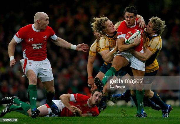 Wales full back Lee Byrne is tackled by Australians Ryan Cross and Peter Hynes during the Invesco Perpetual Series match between Wales and Australia...