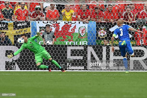 Wales' goalkeeper Danny Ward dives for the ball next to Slovakia's defender Martin Skrtel during the Euro 2016 group B football match between Wales...