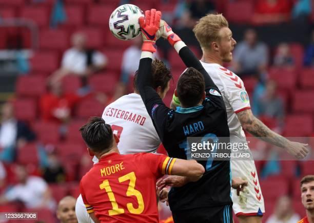 Wales' goalkeeper Danny Ward hands the ball away from Denmark's defender Jannik Vestergaard and Denmark's defender Simon Kjaer during the UEFA EURO...
