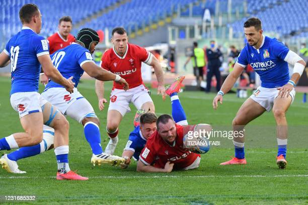 Wales' hooker Ken Owens scores a try despite Italy's center Stephen Varney during the Six Nations rugby union tournament match between Italy and...