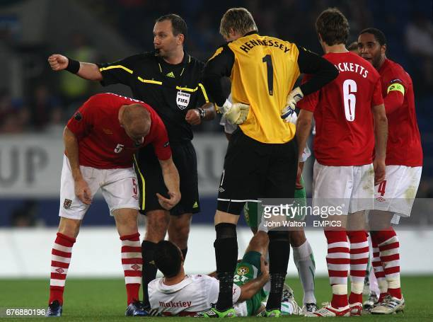 Wales' James Collins gestures to Bulgaria's Dimitar Makriev to get up as the player suffers from cramp on the floor