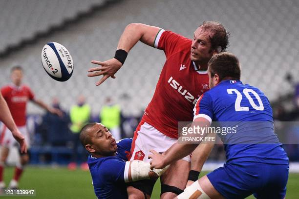 Wales' lock Alun Wyn Jones passes the ball as he is tackeld by France's centre Gael Fickou during the Six Nations rugby union tournament match...