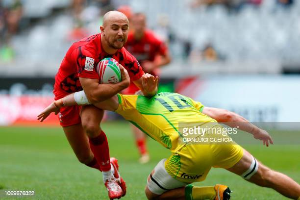 Wales Luke Treharne is tackled by Australia Nick Malouf during the first day of the Rugby Sevens tournament on December 8 at the Cape Town Stadium in...