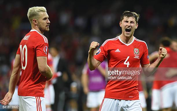 Wales' midfielder Aaron Ramsey and Wales' defender Ben Davies react following their 30 win in the Euro 2016 group B football match between Russia and...