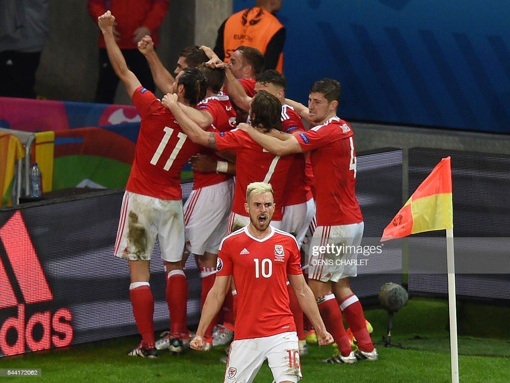 Wales' midfielder Aaron Ramsey (C) celebrates with teammates during the Euro 2016 quarter-final football match between Wales and Belgium at the Pierre-Mauroy stadium in Villeneuve-d'Ascq near Lille, on July 1, 2016. / AFP / DENIS