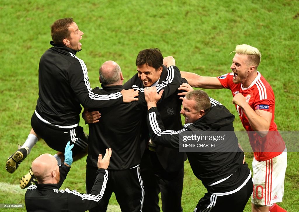 Wales' midfielder Aaron Ramsey (R) celebrates with Wales' coach Chris Coleman (C) and team staff at the end of the Euro 2016 quarter-final football match between Wales and Belgium at the Pierre-Mauroy stadium in Villeneuve-d'Ascq near Lille, on July 1, 2016. / AFP / DENIS