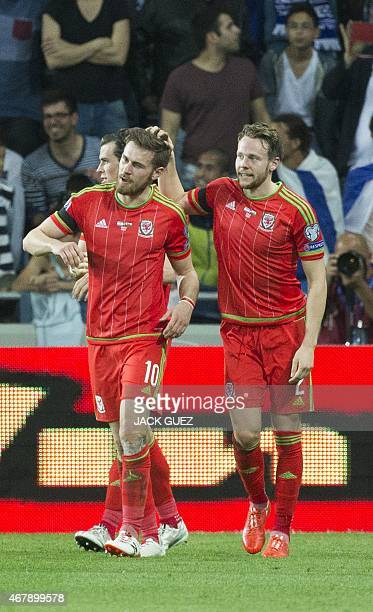 Wales' midfielder Aaron Ramsey is congratulated by his teammate Chris Gunter during the Euro 2016 qualifying football match between Israel and Wales...
