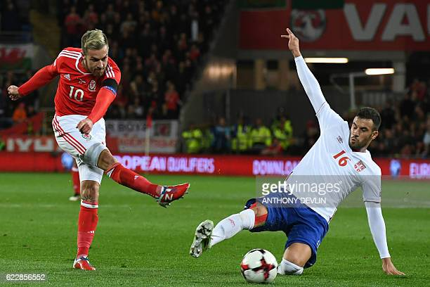 Wales' midfielder Aaron Ramsey shoots past Serbia's midfielder Luka Milivojevic during the World Cup 2018 qualification match between Wales and...