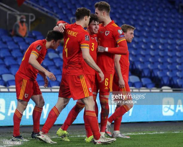 Wales' midfielder Daniel James celebrates scoring the opening goal with teammates during the FIFA World Cup Qatar 2022 qualification football match...