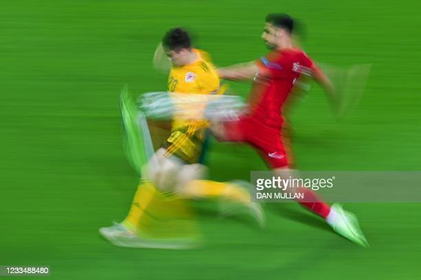 Wales' midfielder Daniel James is challenged by Turkey's forward Cengiz Under during the UEFA EURO 2020 Group A football match between Turkey and...