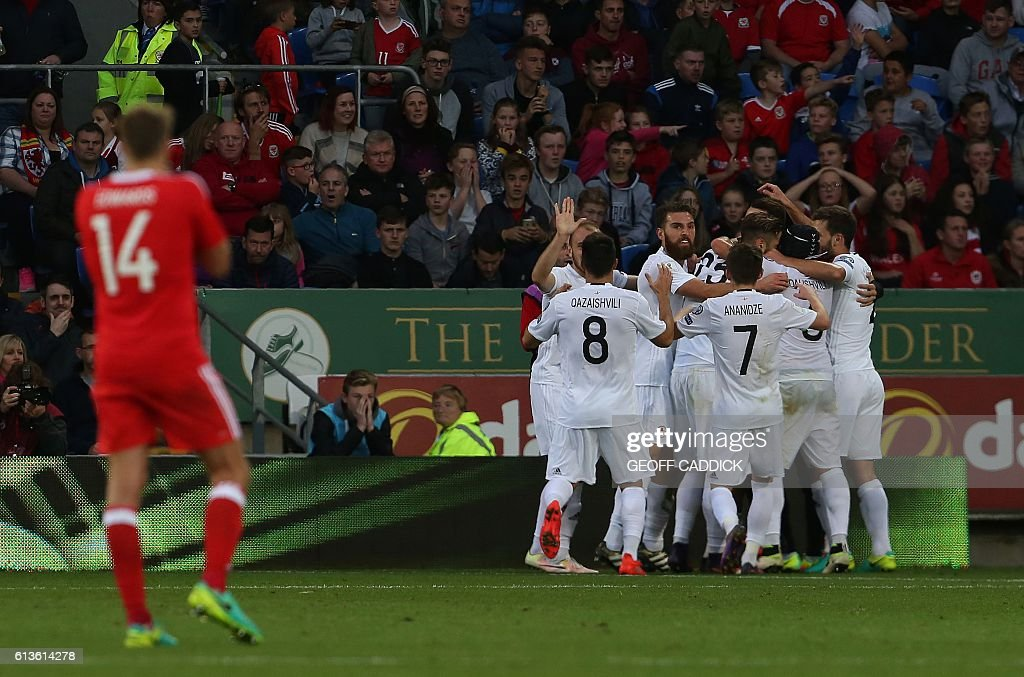 Wales' midfielder David Edwards (L) reacts as Georgia's midfielder Tornike Okriashvili is mobbed by teammates after scoring his team's first goal during the World Cup 2018 football qualification match between Wales and Georgia at Cardiff City Stadium in Cardiff, south Wales on October 9, 2016. / AFP / Geoff CADDICK