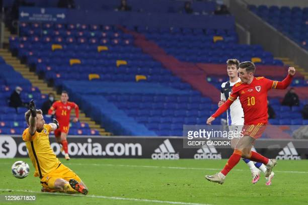 Wales' midfielder Harry Wilson shoots past Finland goalkeeper Lukas Hradecky to score the opening goal of the UEFA Nations League group B4 football...
