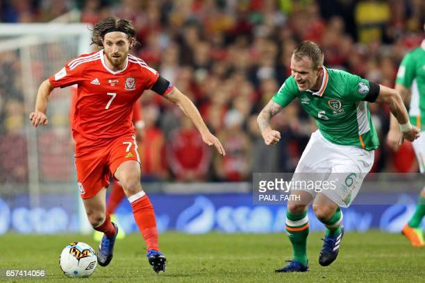 Wales' midfielder Joe Allen runs with the ball chased by Republic of Ireland's midfielder Glenn Whelan during the World Cup 2018 qualification...