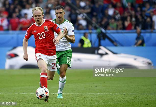 Wales' midfielder Jonathan Williams is challenged by Northern Ireland's defender Aaron Hughes during the Euro 2016 round of sixteen football match...