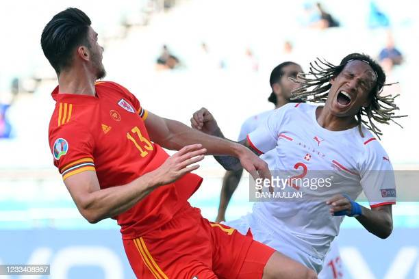 Wales' midfielder Kieffer Moore and Switzerland's defender Kevin Mbabu fall to the ground after a collision during the UEFA EURO 2020 Group A...