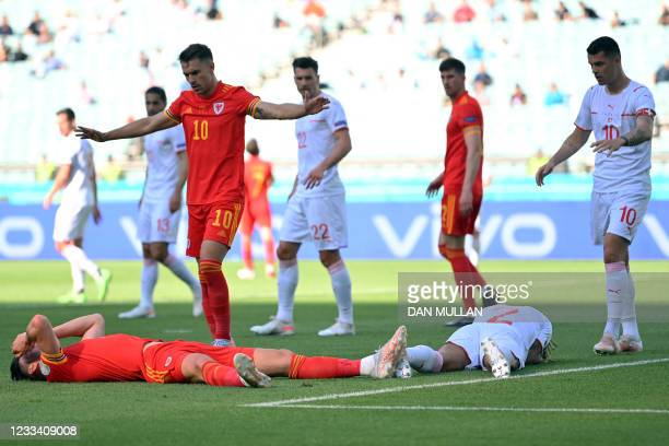 Wales' midfielder Kieffer Moore and Switzerland's defender Kevin Mbabu react on the pitch after a collision during the UEFA EURO 2020 Group A...
