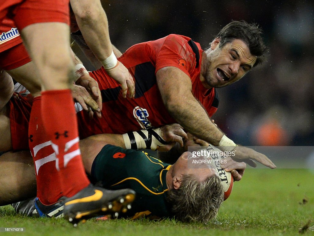 Wales' Mike Phillips (up) tackles South Africa's Jean de Villiers during the International rugby union test match between Wales and South Africa at the Millennium Stadium in Cardiff, south Wales, on November 9, 2013.