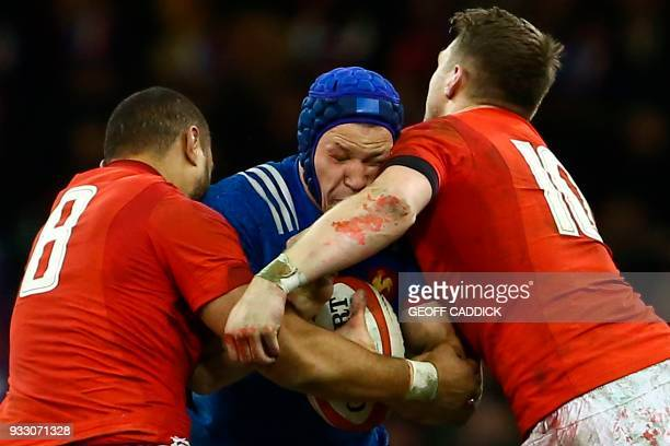 Wales' number 8 Taulupe Faletau and Wales' flyhalf Dan Biggar tackle France's flanker Wenceslas Lauret during the Six Nations international rugby...
