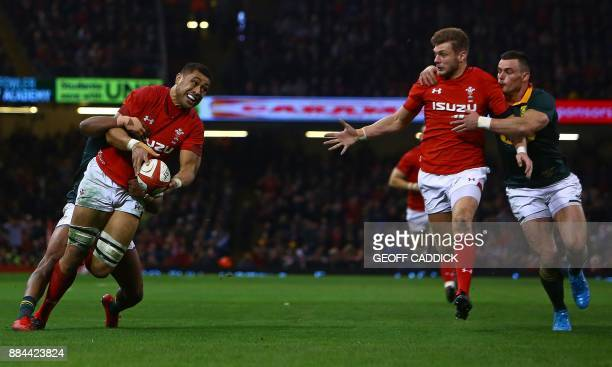Wales' number 8 Taulupe Faletau off loads the ball to Wales' centre Hadleigh Parkes before Parkes went on to score their third try during the...