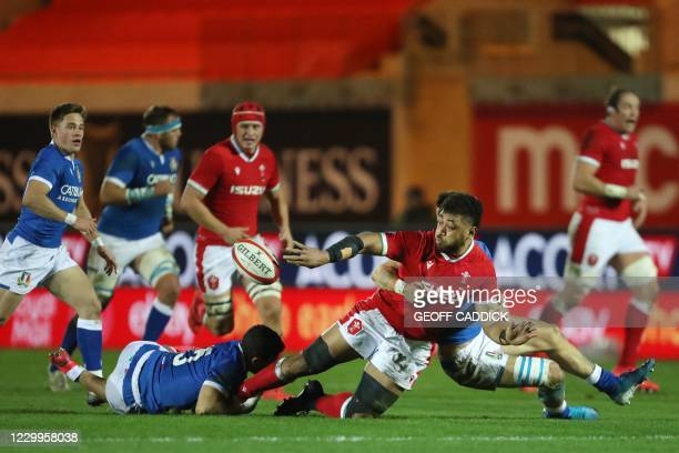 Wales' number 8 Taulupe Faletau offloads the ball as he gets tackled by Italy's full-back Jacopo Trulla during the Autumn Nations Cup international...