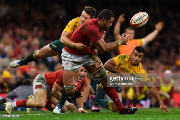 Wales' number 8 Taulupe Faletau releases the ball as he gets dragged into touch during the rugby union international Test match between Wales and...
