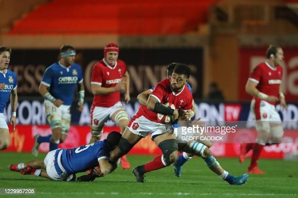 Wales' number 8 Taulupe Faletau runs with the ball as he gets tackled by Italy's full-back Jacopo Trulla during the Autumn Nations Cup international...