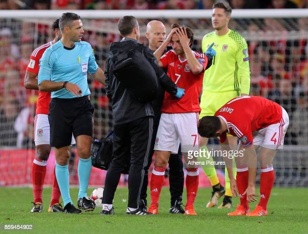 Wales physiotherapists see to Joe Allen who suffered a suspected head injury during the FIFA World Cup Qualifier Group D match between Wales and...