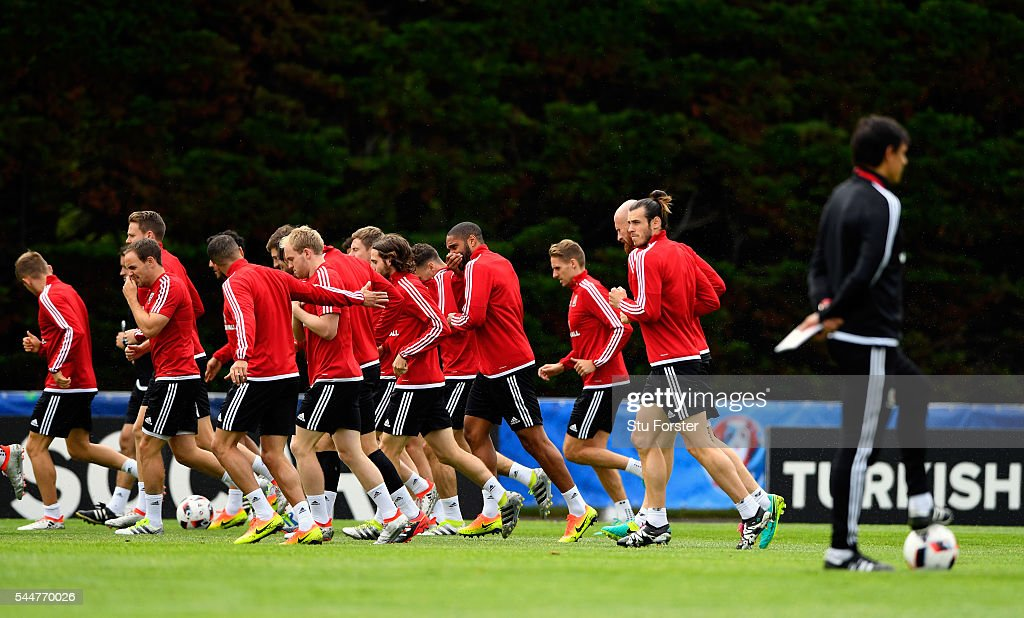 Wales player Gareth Bale (2nd r) and team mates do a warm up run as manager Chris Coleman looks on during Wales training ahead of their UEFA Euro 2016 semi final against Portugal at College Le Bocage on July 4, 2016 in Dinard, France.
