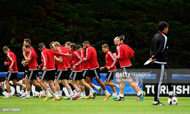 Wales player Gareth Bale and team mates do a warm up run as manager Chris Coleman looks on during Wales training ahead of their UEFA Euro 2016 semi...