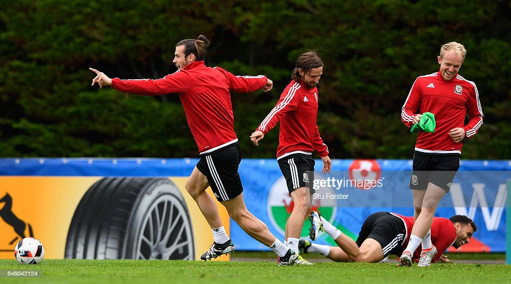Wales player Gareth Bale (l) laughs with Joe Allen, Jonny Williams and Hal Robson-Kanu (floor) during Wales training ahead of their UEFA Euro 2016 Semi final against Portugal at College Le Bocage on July 5, 2016 in Dinard, France.