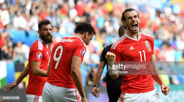 Wales player Gareth Bale of Wales celebrates his team's second goal scored by Hal RobsonKanu as Joe Ledley looks on during the UEFA EURO 2016 Group B...