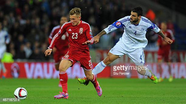 Wales player George Williams is challenged by Giorgos Merkis of Cyprus during the EURO 2016 Qualifier match between Wales and Cyprus at Cardiff City...