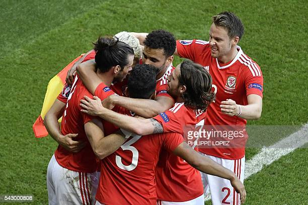 Wales' players celebrate after an own goal by Northern Ireland's defender Gareth McAuley during the Euro 2016 round of sixteen football match Wales...